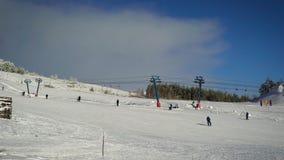 Άποψη της κλίσης σκι Ο υπαίθριος χειμώνας και ο κρύος καιρός, έτσι οι άνθρωποι που κυλούν να κάνουν σκι έντυσαν θερμά στο θόριο απόθεμα βίντεο