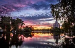 Άποψη της λίμνης, του ουρανού, των δέντρων απόλυσης και της εκκλησίας στην επισκευή στο ηλιοβασίλεμα Στοκ Φωτογραφίες