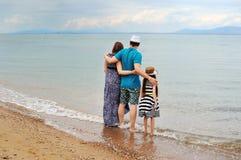 Άποψη της νέας οικογένειας που έχει τη διασκέδαση στην παραλία στοκ εικόνα