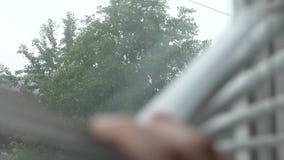 Άποψη της οδού κατά τη διάρκεια της βροχής μέσω των τυφλών στο παράθυρο r απόθεμα βίντεο