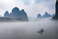 άποψη της ομίχλης με τα σκάφη στον ποταμό κοντά στην πόλη Xingping Στοκ Εικόνες