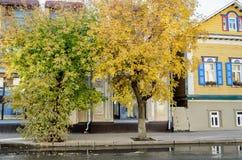 Άποψη της οδού με τα δέντρα φθινοπώρου και του ξύλινου σπιτιού στο ρωσικό ύφος στοκ εικόνες