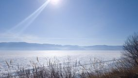 Άποψη της παγωμένης λίμνης Baikal και του χιονιού στον πάγο Μια ηλιόλουστη ημέρα την άνοιξη, Σιβηρία στη Ρωσία στοκ φωτογραφία