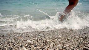 Άποψη της παραλίας στην οποία τα πόδια του κοριτσιού πλένονται από την ελαφριά κυματωγή θάλασσας απόθεμα βίντεο