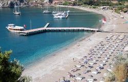 Άποψη της παραλίας, της μπλε λιμνοθάλασσας με το σαφές νερό και μιας αποβάθρας με Στοκ Φωτογραφίες