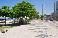 Άποψη της παραλίας Barra DA Tijuca με τους φοίνικες και του μωσαϊκού του πεζοδρομίου στοκ εικόνα