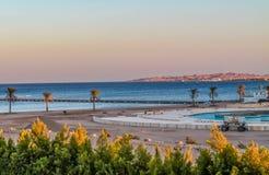 Άποψη της περιοχής αναψυχής hotel's στην παραλία και την ακροθαλασσιά, φοίνικες κάτω από το μπλε ουρανό μιας ηλιόλουστης ημέρας στοκ φωτογραφία με δικαίωμα ελεύθερης χρήσης