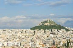Άποψη της πόλης της Αθήνας, και ένα μεγάλο βουνό με ένα μοναστήρι στην κορυφή όμορφος μπλε ουρανός στοκ εικόνα