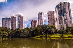 Άποψη της πόλης, του σύγχρονου κτηρίου μεταξύ του ουρανού και μιας λίμνης στοκ εικόνα με δικαίωμα ελεύθερης χρήσης