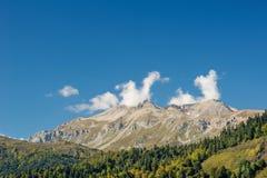 Άποψη της υψηλής κορυφογραμμής των βουνών Καύκασου και του δάσους στο πόδι Στοκ Φωτογραφίες