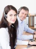 Άποψη της όμορφης νέας επιχειρηματία και του όμορφου επιχειρηματία στις κάσκες που χρησιμοποιούν τα lap-top στο γραφείο callcente στοκ φωτογραφία με δικαίωμα ελεύθερης χρήσης