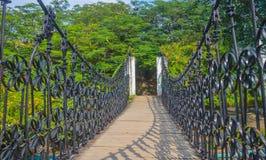 Άποψη τοπίων της μακριάς γέφυρας αναστολής χάλυβα επάνω από το κανάλι σε μια ζούγκλα Αρχή μιας περιπέτειας, δρόμος στη ζούγκλα Στοκ Φωτογραφίες