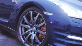 Άποψη του δίσκου ροδών του σκούρο μπλε νέου αυτοκινήτου Παρουσίαση προβολείς ηλιαχτίδες automatism Κρύα σκιά απόθεμα βίντεο
