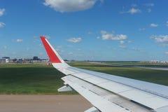 Άποψη του αερολιμένα και των αεροσκαφών, του μπλε ουρανού και των σύννεφων από το φωτιστικό επιβατηγών αεροσκαφών επιβατών στοκ φωτογραφία