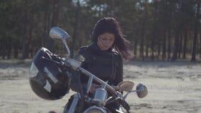 άποψη του αρκετά καυκάσιου κοριτσιού σε μια μαύρη συνεδρίαση σακακιών δέρματος στο βιβλίο ανάγνωσης μοτοσικλετών Χόμπι φιλμ μικρού μήκους