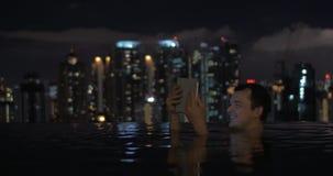 Άποψη του ατόμου στην πισίνα στη στέγη ουρανοξυστών που χρησιμοποιεί την ταμπλέτα ενάντια στο τοπίο πόλεων νύχτας Κουάλα Λουμπούρ απόθεμα βίντεο