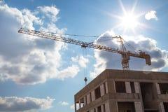 Άποψη του γερανού κατασκευής στην κατασκευή του σπιτιού μια σαφή ηλιόλουστη ημέρα, το backlight στοκ φωτογραφία με δικαίωμα ελεύθερης χρήσης