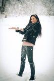 Άποψη του ευτυχούς παιχνιδιού κοριτσιών brunette με το χιόνι στο χειμερινό τοπίο Όμορφο νέο θηλυκό στο χειμερινό υπόβαθρο Ελκυστι Στοκ Εικόνα