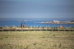 Άποψη του ζεύγους που περπατά στη για τους πεζούς ξύλινη διάβαση πεζών, κοντά στη θάλασσα στοκ εικόνες