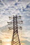 Άποψη του ηλεκτροφόρου καλωδίου ενάντια στα σύννεφα του μπλε ουρανού στο φως του ήλιου στοκ εικόνα