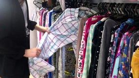 Άποψη του καυκάσιου έφηβη που επιλέγει τα ενδύματα στο κατάστημα χεριών Α δεύτερος φιλμ μικρού μήκους