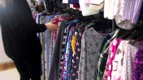 Άποψη του καυκάσιου έφηβη που επιλέγει τα ενδύματα στο κατάστημα χεριών Α δεύτερος απόθεμα βίντεο