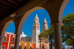 Άποψη του κύριου πάρκου μέσω της αψίδας του κτηρίου βιβλιοθηκών Campeche, Μεξικό Στο υπόβαθρο είναι ο καθεδρικός ναός del Λα συμπ στοκ εικόνα