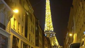 Άποψη του λαμπιρίζοντας πύργου του Άιφελ από την οδό με την ευρωπαϊκή αρχιτεκτονική τη νύχτα φιλμ μικρού μήκους