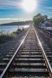 Άποψη του μήκους της διαδρομής σιδηροδρόμων με τις λαμπρές ακτίνες φωτός του ήλιου, τον ποταμό, τα απόμακρες βουνά και την πρασιν στοκ εικόνες