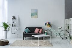 άποψη του μοντέρνου καθιστικού με το αναδρομικό ποδήλατο, τραπεζάκι σαλονιού Στοκ φωτογραφίες με δικαίωμα ελεύθερης χρήσης