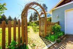 Άποψη του ξύλινου άξονα Σχηματισμένη αψίδα είσοδος στον κήπο στοκ εικόνα με δικαίωμα ελεύθερης χρήσης