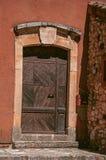 Άποψη του παραδοσιακού ζωηρόχρωμου σπιτιού στο ocher και την ξύλινη πόρτα, στη Roussillon στοκ εικόνες