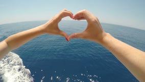 Άποψη του ρομαντικού ζεύγους που διαμορφώνει τη μορφή καρδιών με τα δάχτυλα που πλέουν με τη βάρκα κρουαζιέρας - απόθεμα βίντεο