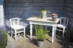 Άποψη του σπιτιού κήπων τα άσπρα αναδρομικά ξύλινα έπιπλα που διακοσμούνται με με τα δοχεία λουλουδιών Στοκ Εικόνα