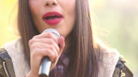 Άποψη του στόματος της γυναίκας με το κόκκινο κραγιόν, που χαμογελά και που τραγουδά με το μικρόφωνο απόθεμα βίντεο