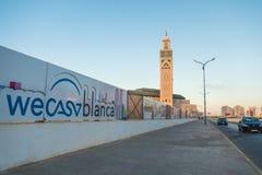 άποψη του Χασάν ΙΙ μουσουλμανικό τέμενος από την οδό και τους πίνακες διαφημίσεων που παρουσιάζουν λογότυπο Wecasablanca Στοκ φωτογραφία με δικαίωμα ελεύθερης χρήσης