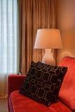 Άποψη του δωματίου γωνιών με ένα τέλος καναπέδων και του δευτερεύοντος πίνακα με τον επιτραπέζιο λαμπτήρα Στοκ Φωτογραφίες
