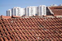 Άποψη των αστικών κτηρίων μετασχηματισμού πέρα από μια παλαιά στέγη σπιτιών Στοκ Εικόνα