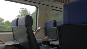 Άποψη των ατόμων στο τραίνο και της εργασίας με το lap-top στον πίνακα και της κατανάλωσης ενάντια στο παράθυρο, Κάτω Χώρες απόθεμα βίντεο