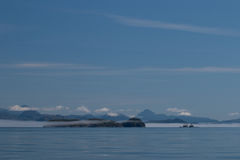 Άποψη των βουνών και των χαμηλών άσπρων σύννεφων πριν από το μπλε ουρανό και απεικόνιση της ήρεμης θάλασσας του Καναδά ` s μέσα σ Στοκ Εικόνες