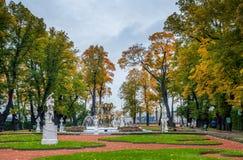Άποψη των δέντρων φθινοπώρου, αρχαία μαρμάρινα αγάλματα, χορτοτάπητας, πηγή και Στοκ εικόνα με δικαίωμα ελεύθερης χρήσης