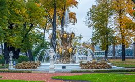 Άποψη των δέντρων φθινοπώρου, των αρχαίων μαρμάρινων αγαλμάτων, του χορτοτάπητα και του καταρράκτη φ Στοκ φωτογραφία με δικαίωμα ελεύθερης χρήσης
