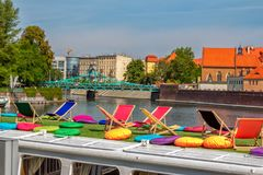 Άποψη των καθεδρικών ναών νησιών Tumski μέσω της τουριστικής γέφυρας βαρκών με τις ζωηρόχρωμα καρέκλες και τα μαξιλάρια Στοκ εικόνα με δικαίωμα ελεύθερης χρήσης