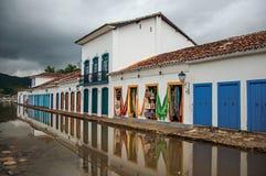 Άποψη των καταστημάτων στα παλαιά σπίτια στην αλέα με την πλημμυρισμένη διάβαση πεζών πετρών σε Paraty στοκ φωτογραφία με δικαίωμα ελεύθερης χρήσης