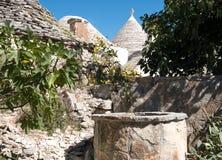 Άποψη των κωνικών στεγών ξηρών πετρών μιας ομάδας παραδοσιακών σπιτιών trulli σε Alberobello στην Πούλια Ιταλία στοκ φωτογραφίες