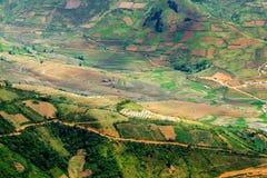 Άποψη των πεζουλιών ρυζιού που αντιμετωπίζονται από μια αιχμή βουνών Στοκ Εικόνες