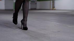 Άποψη των ποδιών της περπατώντας γυναίκας στις μαύρες γυναικείες κάλτσες και των υψηλών τακουνιών στο χώρο στάθμευσης απόθεμα βίντεο