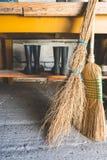 Άποψη των σκουπών και δύο ζευγάρια των λαστιχένιων μποτών στο πλαίσιο ενός πίνακα μέσα σε ένα δωμάτιο αποθήκευσης στοκ φωτογραφία με δικαίωμα ελεύθερης χρήσης