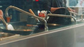 Άποψη των χεριών μαγείρων ` s που προετοιμάζουν τα κινεζικά τρόφιμα στο wok στο εστιατόριο στην αγορά boqueria απόθεμα βίντεο