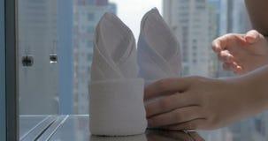 Άποψη των χεριών που βάζουν τις πετσέτες ξενοδοχείων στο λουτρό με το υπόβαθρο πόλεων απόθεμα βίντεο